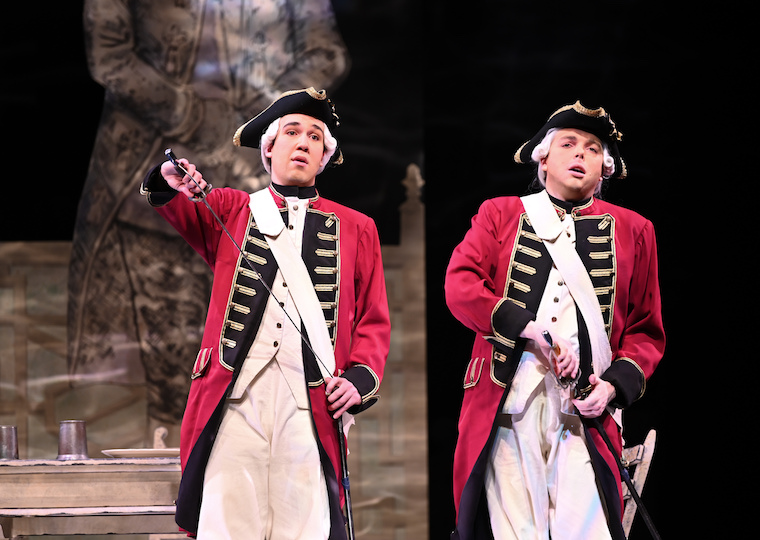 Two men in 18th century military uniforms sing on stage.