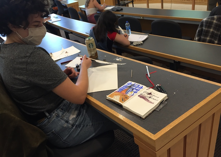 A student looks at a handmade journal on a table.