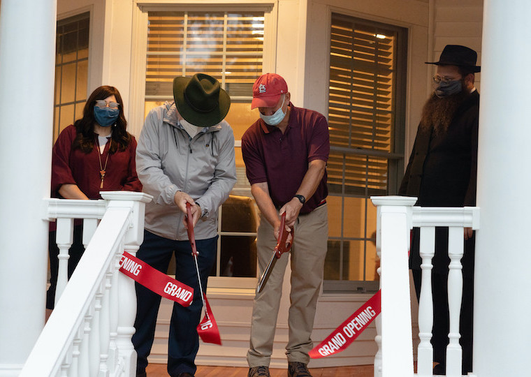 Two men use two sets of large scissors to cut a ribbon.