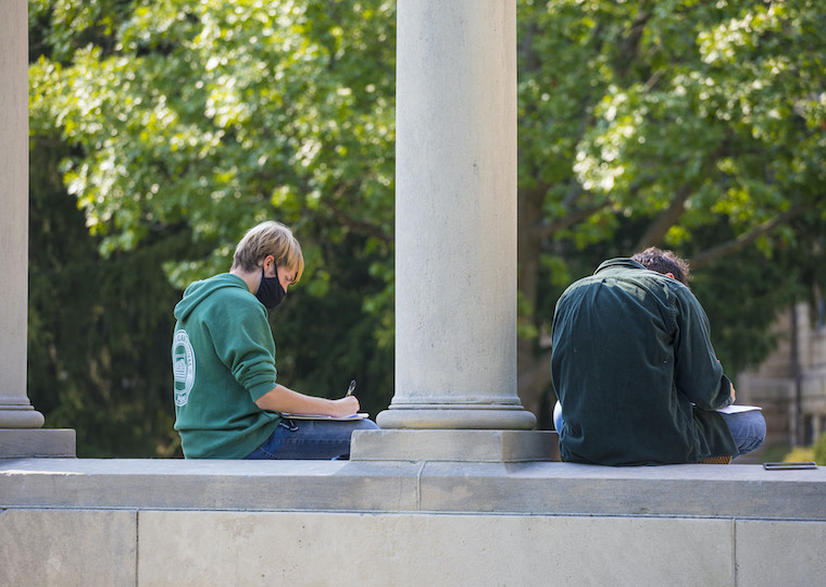 Two students study while sitting on a large memorial arch.