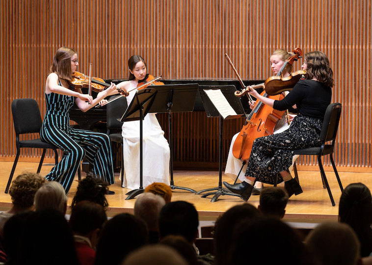 A student quartet plays on stage.
