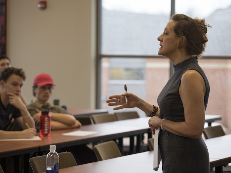 A woman talks to a group of students.