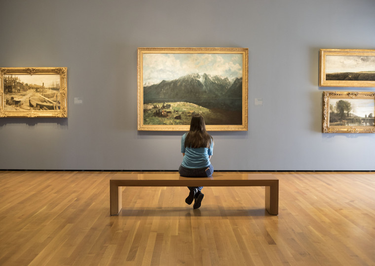 A student looks at a painting in a museum while sitting on a bench.