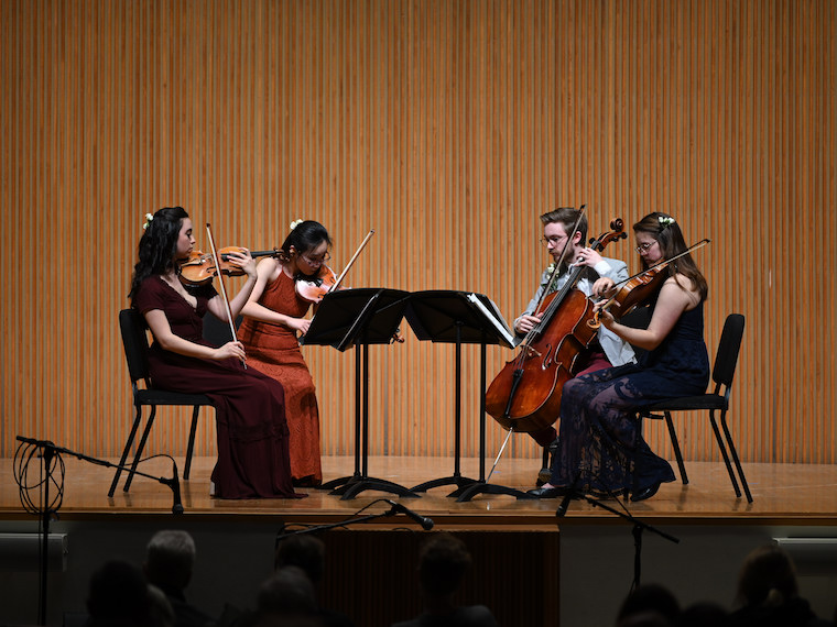 Four students play stringed instruments on stage.