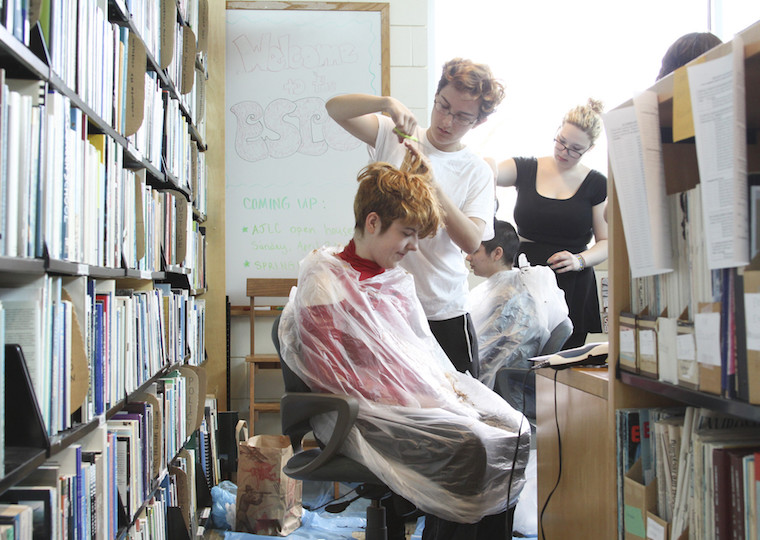 Students cut hair in a library.
