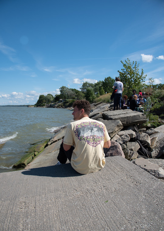 A person sitting on a large rock looks out at Lake Erie.