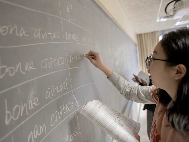 A student writes Latin on a chalkboard.