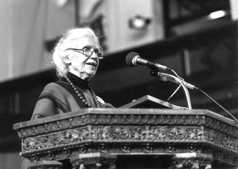 An elderly woman speaks at a podium.