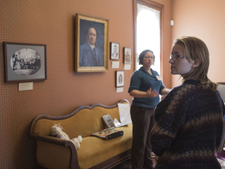 A student looks over her shoulder at a picture during a tour of an old home.