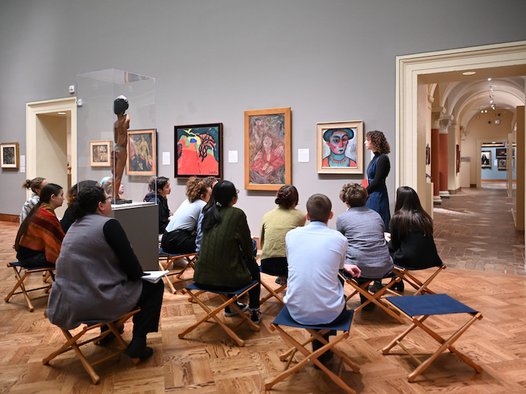 A student gives a gallery talk to her peers in an art museum.