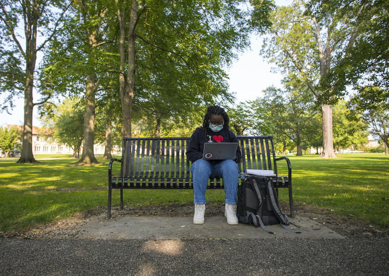 A girl sits on a bench and studies in the park.