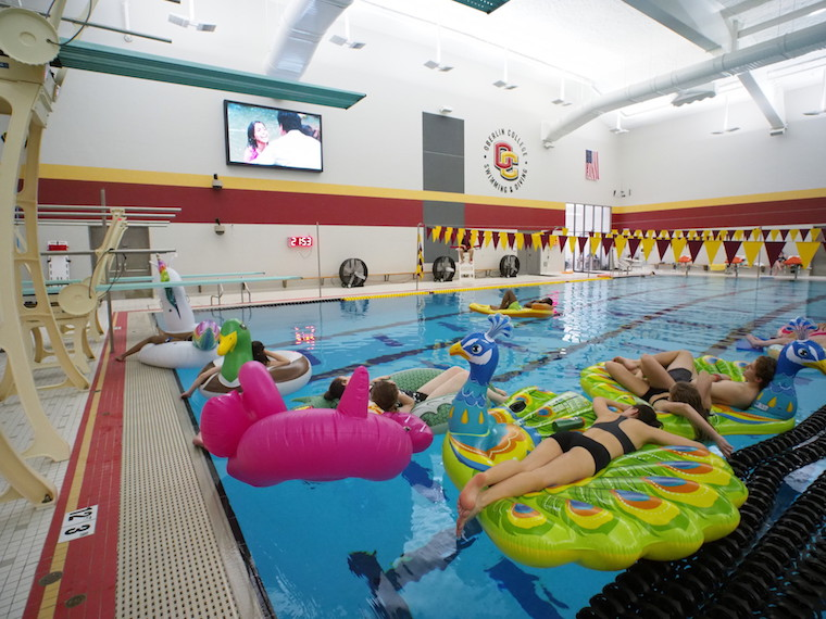 Students rest on floats in a pool and watch a movie on a large screen.