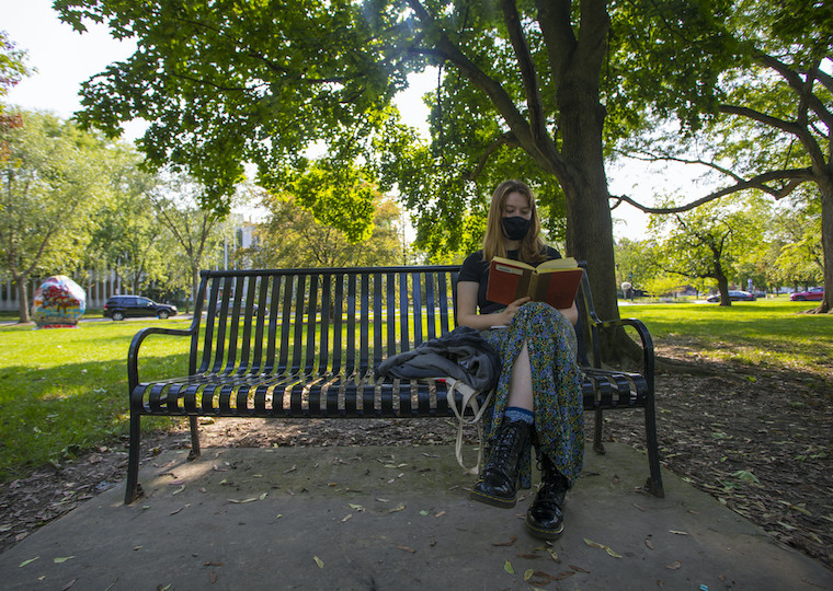 A student sits on a bench and reads in the park.