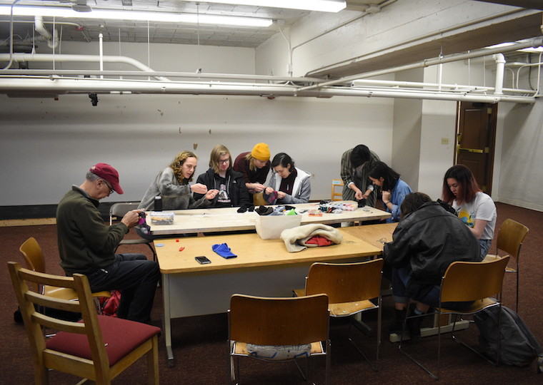 A group of students learn how to sew.
