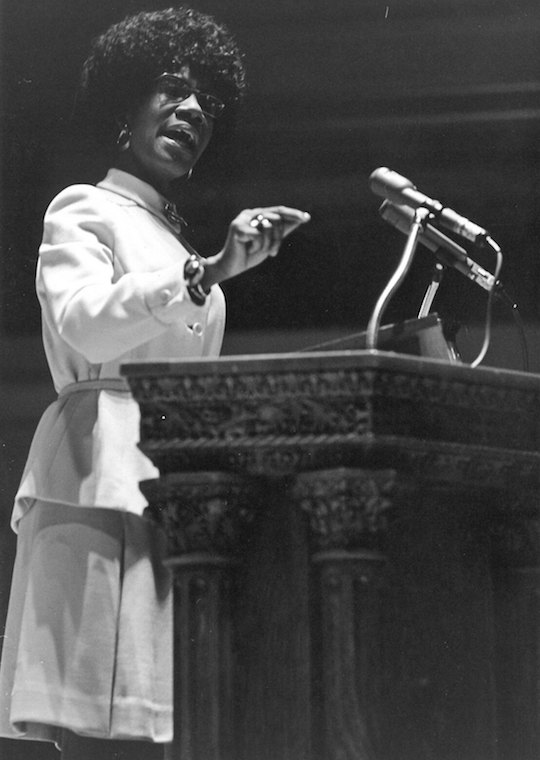 An African American woman speaks at a podium.