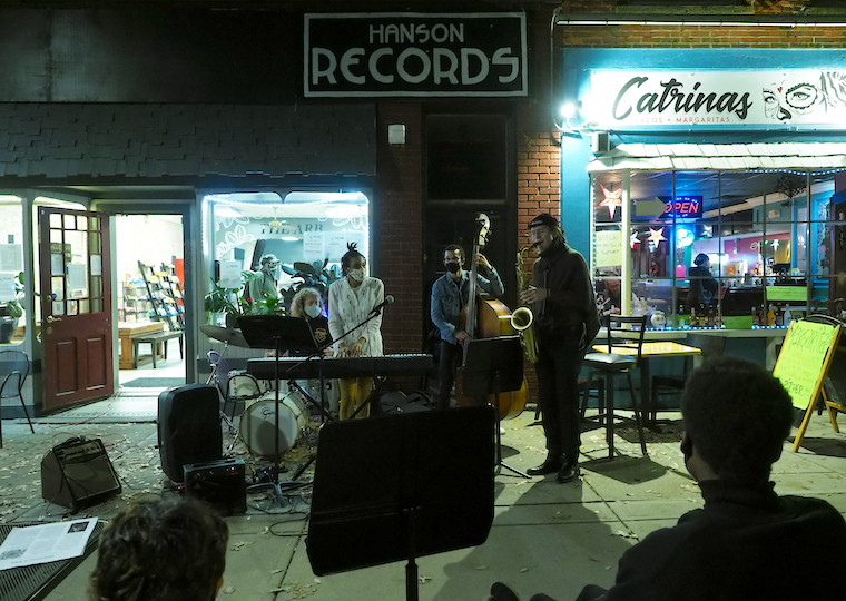 Student musicians play jazz on the sidewalk at night.