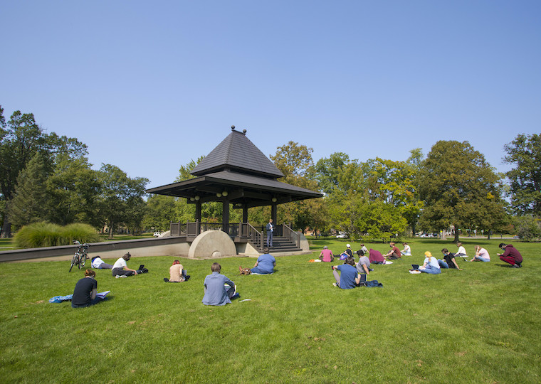 A large class sits on the grass in the park facing a large gazebo.