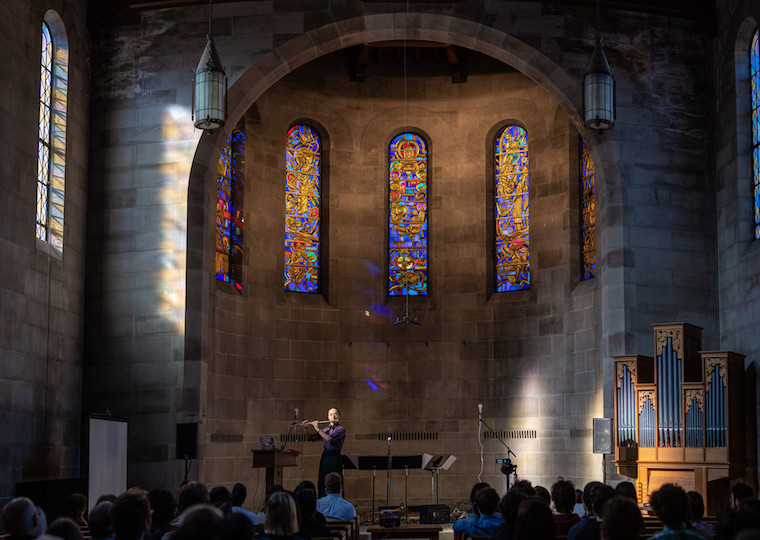A flutist plays in a stone church.