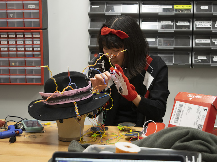 A girl places flexible wires on a hat.
