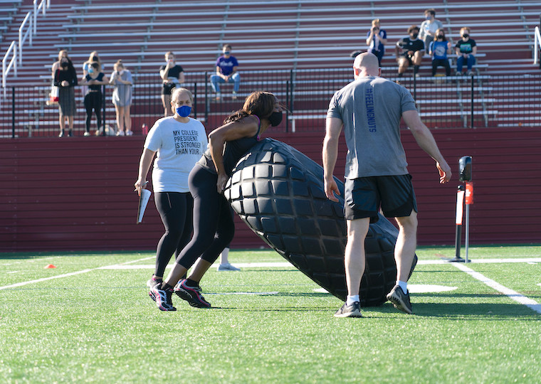 A woman tries to flip over a truck tire on a football field.