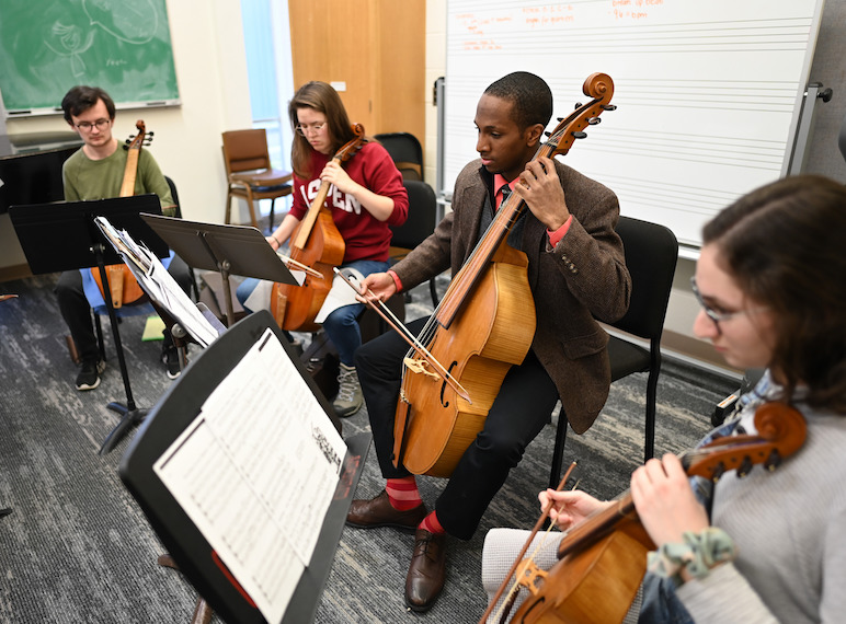 Students play the viola in a small studio.