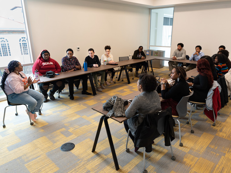A group of students sit facing a graduate student in a conference room.