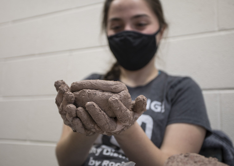 A girl holds a wet clay pot