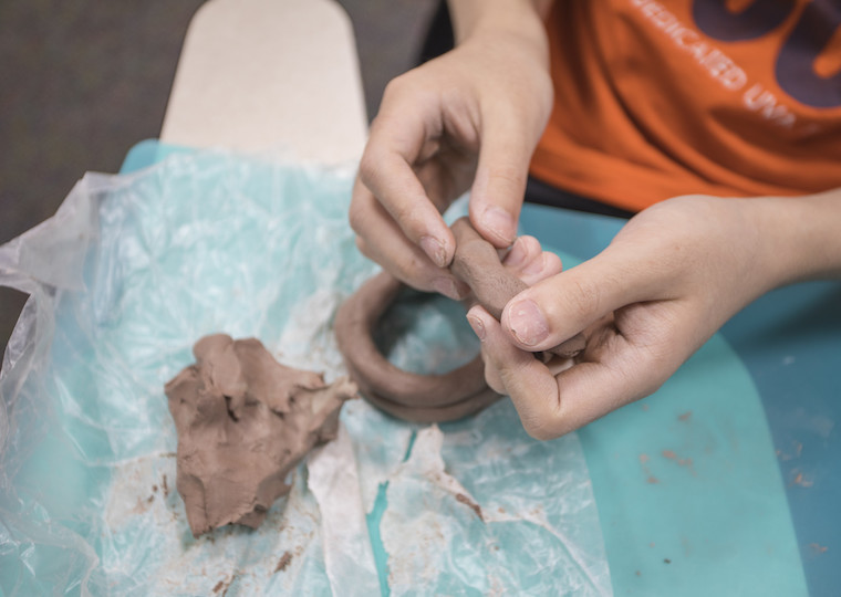 Hands of a student hold a long piece of clay.