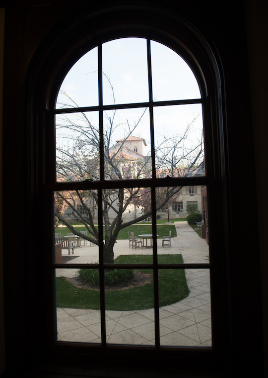 An arched window overlooks a courtyard.