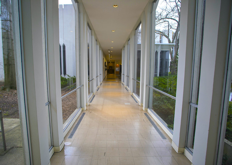 A corridor is flanked by windows.