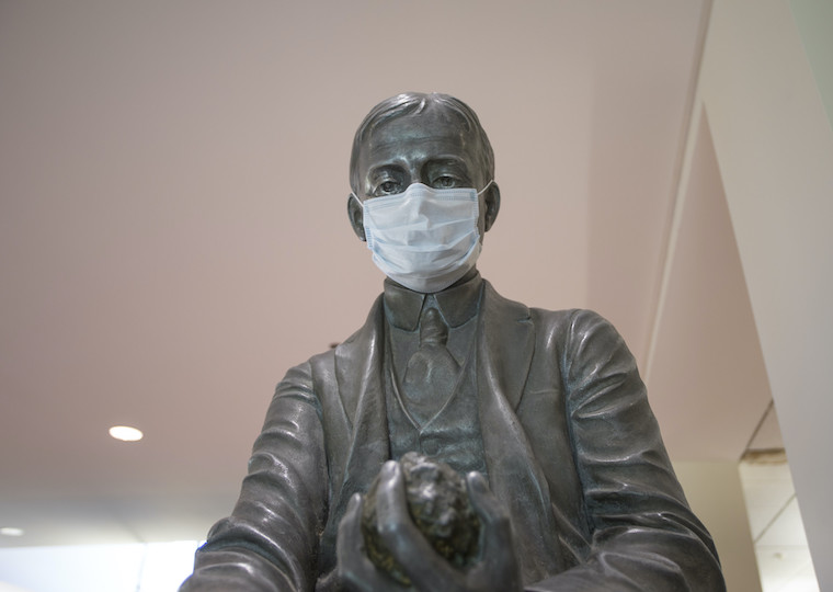 A statue of a man wearing a face mask.