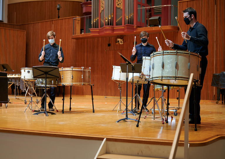 Three students play kettle drums on a stage.