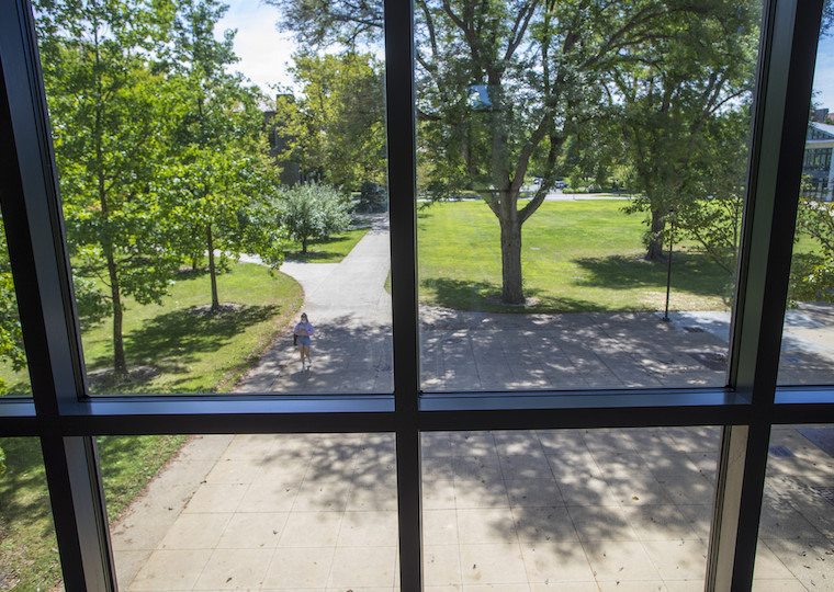 A view through a large window of a student walking on a sidewalk