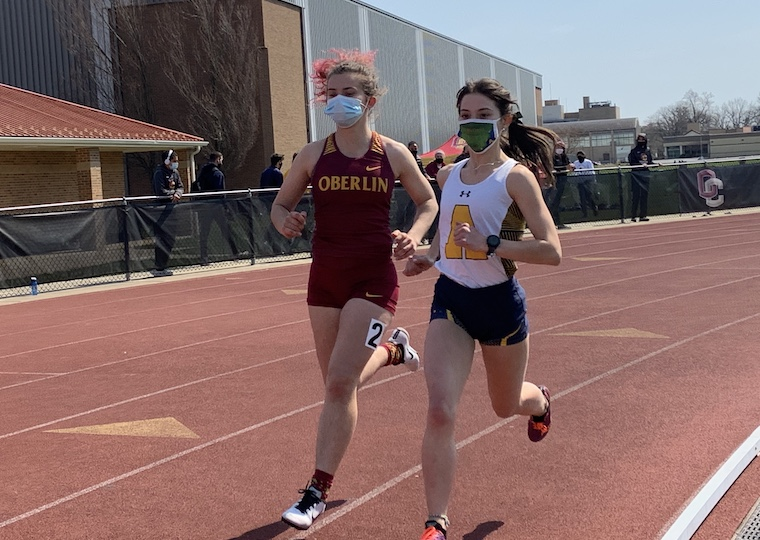 Two female college students race in a track meet.