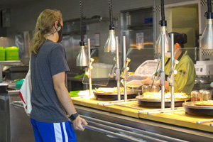 A lone studentpicks up a meal while a worker behind plexiglass prepares food. They are wearing masks and are physically distant.