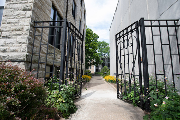 An open, wrought-iron gate between 2 campus buildings.