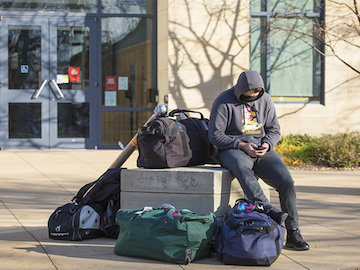A student with luggage waits outside a dorm.