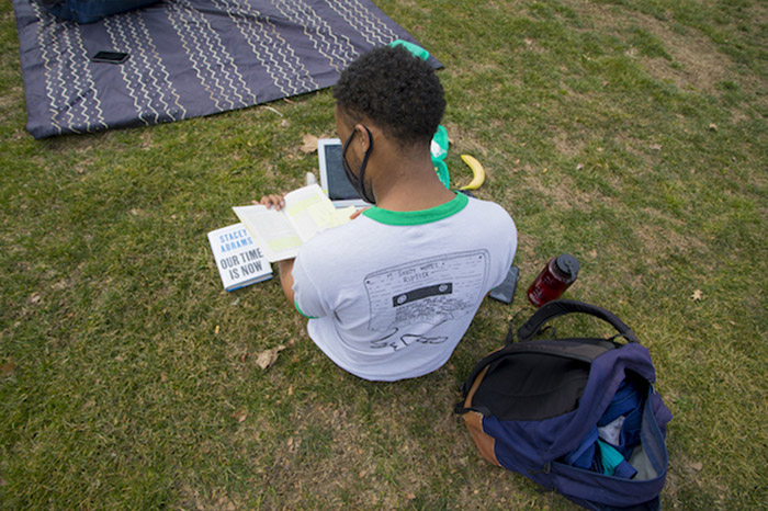 A masked student reads while sitting on the grass.