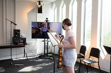 A violist in a sunny room. Her professor is shown on a TV screen.