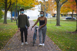 Two students wearing masks stroll through Tappan Square