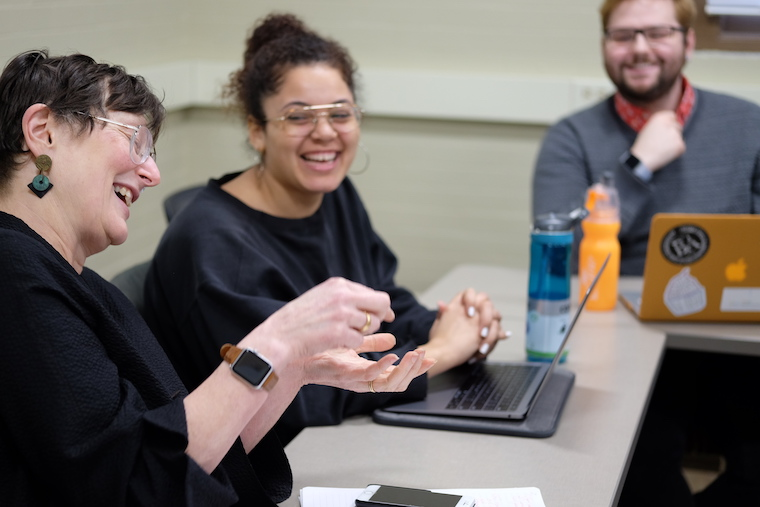 Image of Nancy Darling laughing and talking with students in her research group