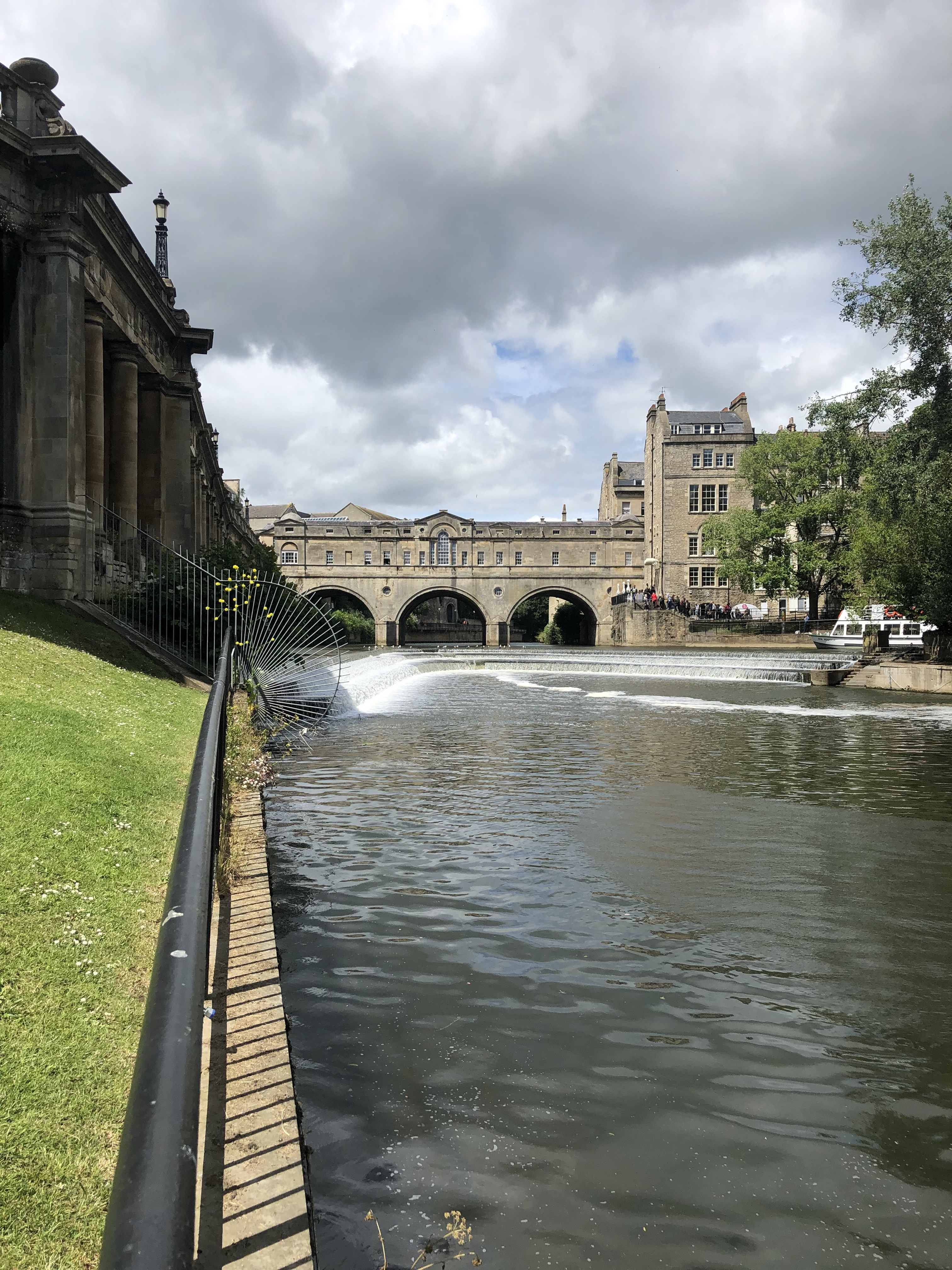 Pictured is a lightly flowing river cutting through a park on a clear summer day. In the middle of the picture is a vaulted bridge going over the river. The sky is fairly cloudy, but the day is still quite sunny