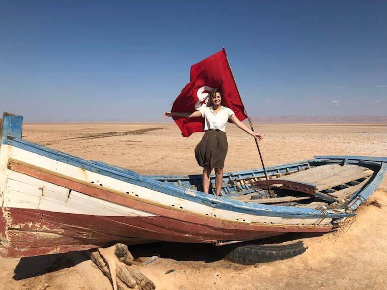 Student stands on a sailboat in a desert