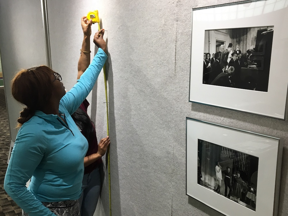students hanging photographs on a gallery wall
