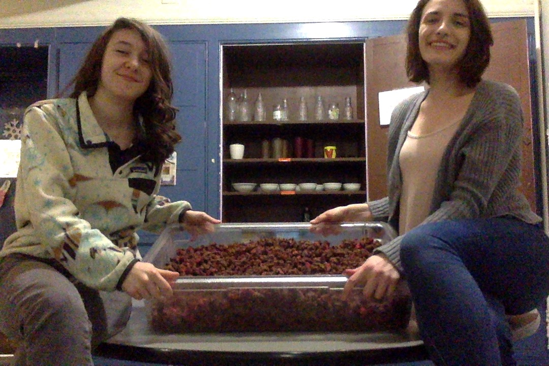 Megan and Lily sit on the tasty things table in Fairchild, holding their uncovered container of granola and tilting it toward the camera. They are smiling.