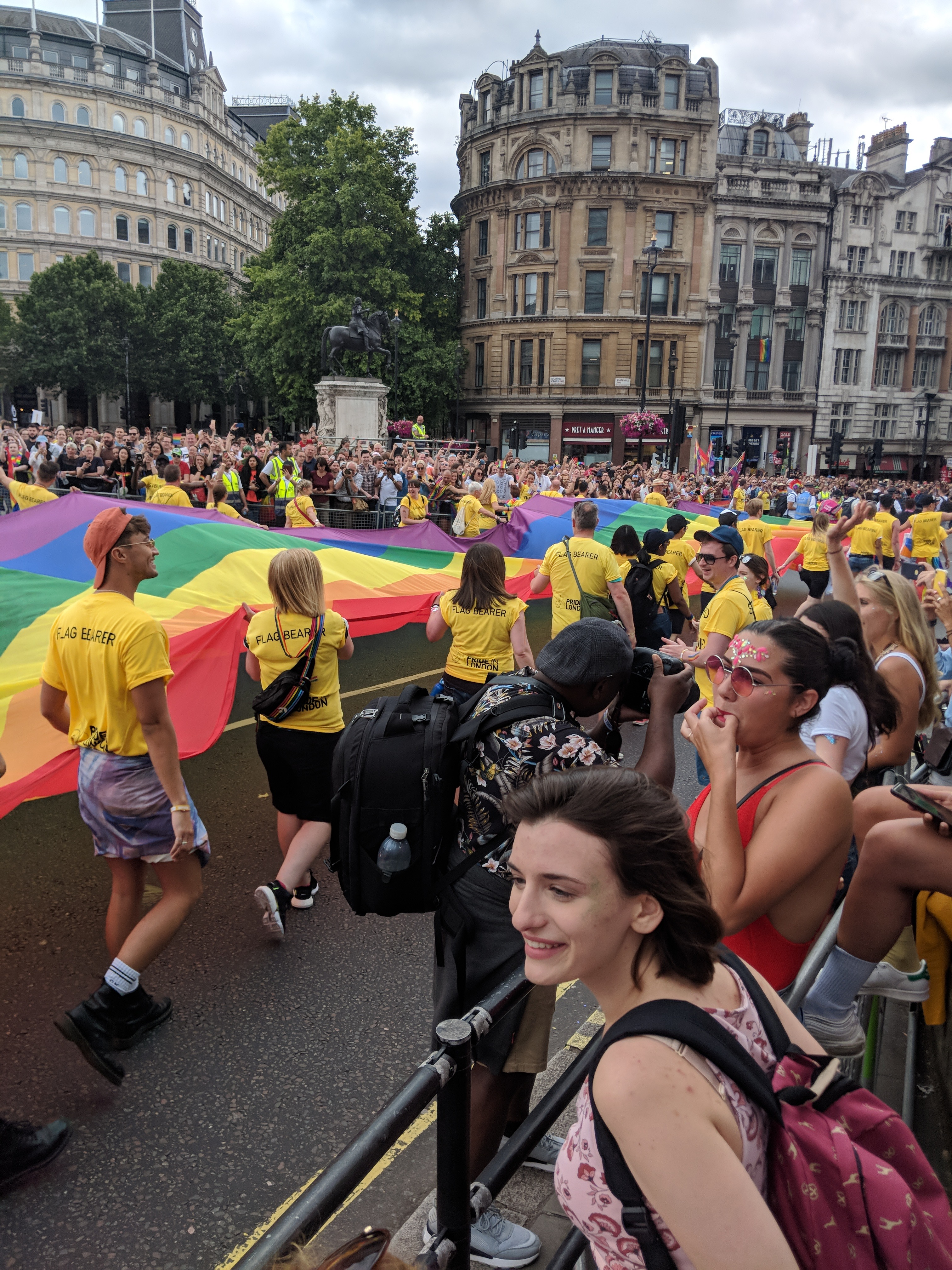 People crowd either side of the street, including me, who is pictured watching the procession right at the edge of the street. Proceeding down the street are people in yellow shirts all holding onto a rainbow flag. In the background of the crowds of people are some historic looking buildings, and a statue of a man riding a horse