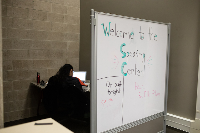 A whiteboard has a handwritten message: Welcome to the speaking center! Hours: Su, T, Th 7-9 pm. On staff tonight: Carrie.