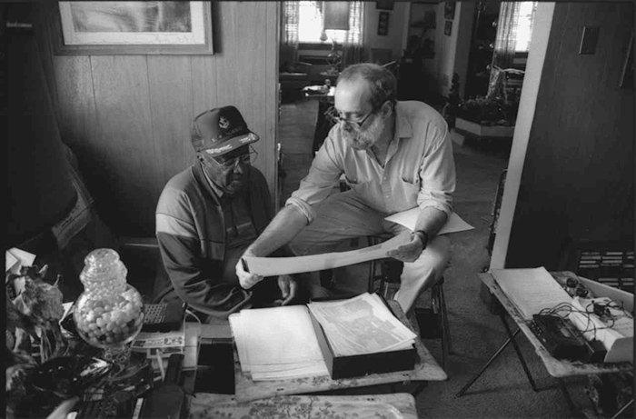 Two men examine a photo in a home office
