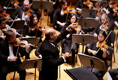 A violin section plays while the conductor raises his baton