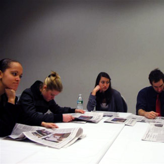 Students around a table examining newspapers